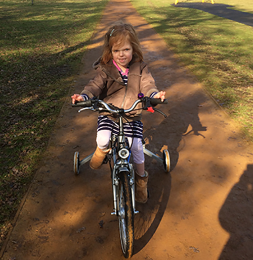 Hope rides her adapted trike