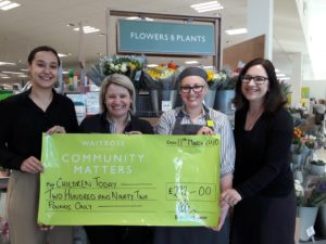 Waitrose employees present a cheque to Rachel (left) and Emma (right) of Children Today